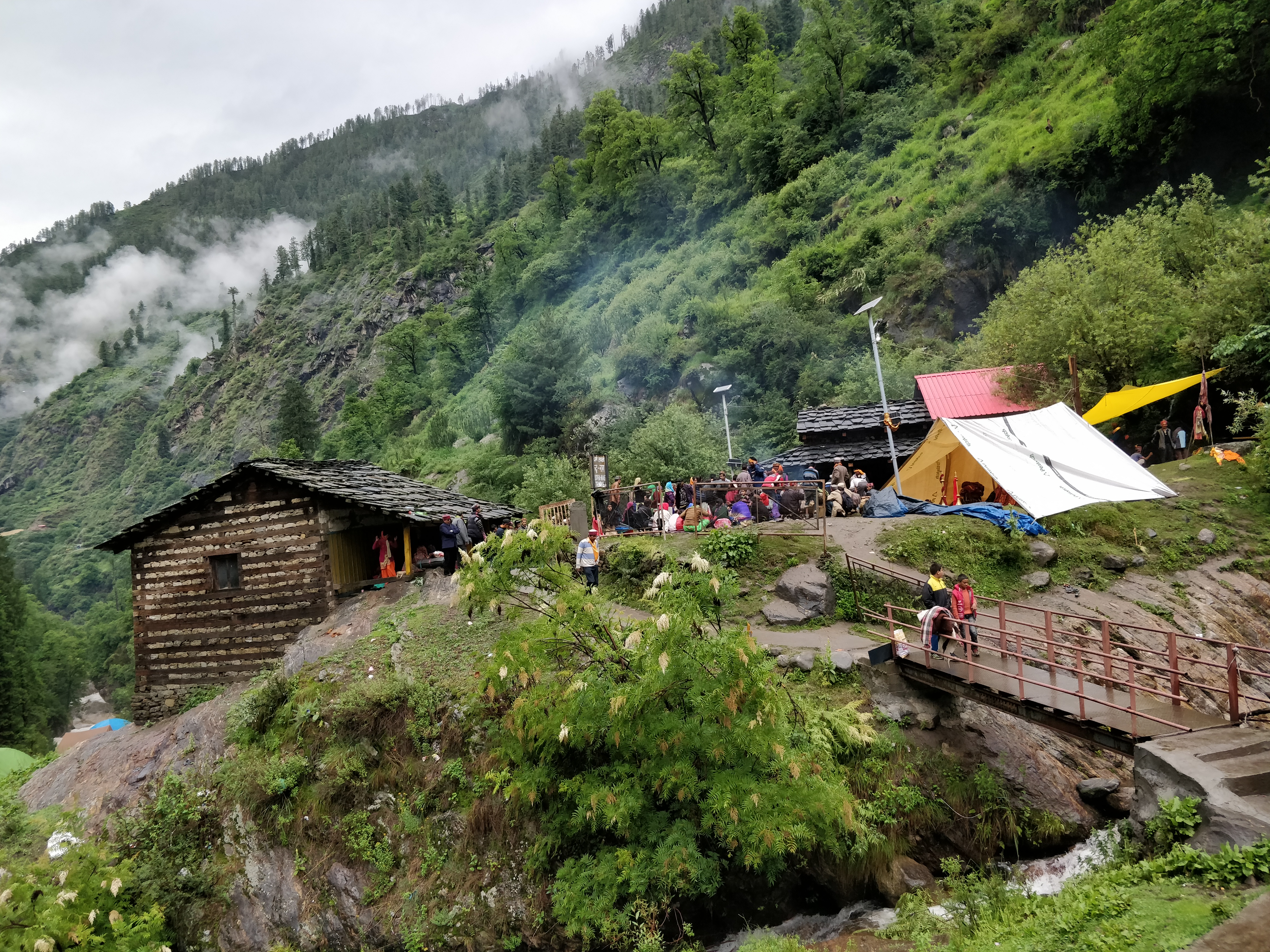 The view of a bridge over the Parvati River surrounded by the mountains on the way to the summint on Kheerganga Trek