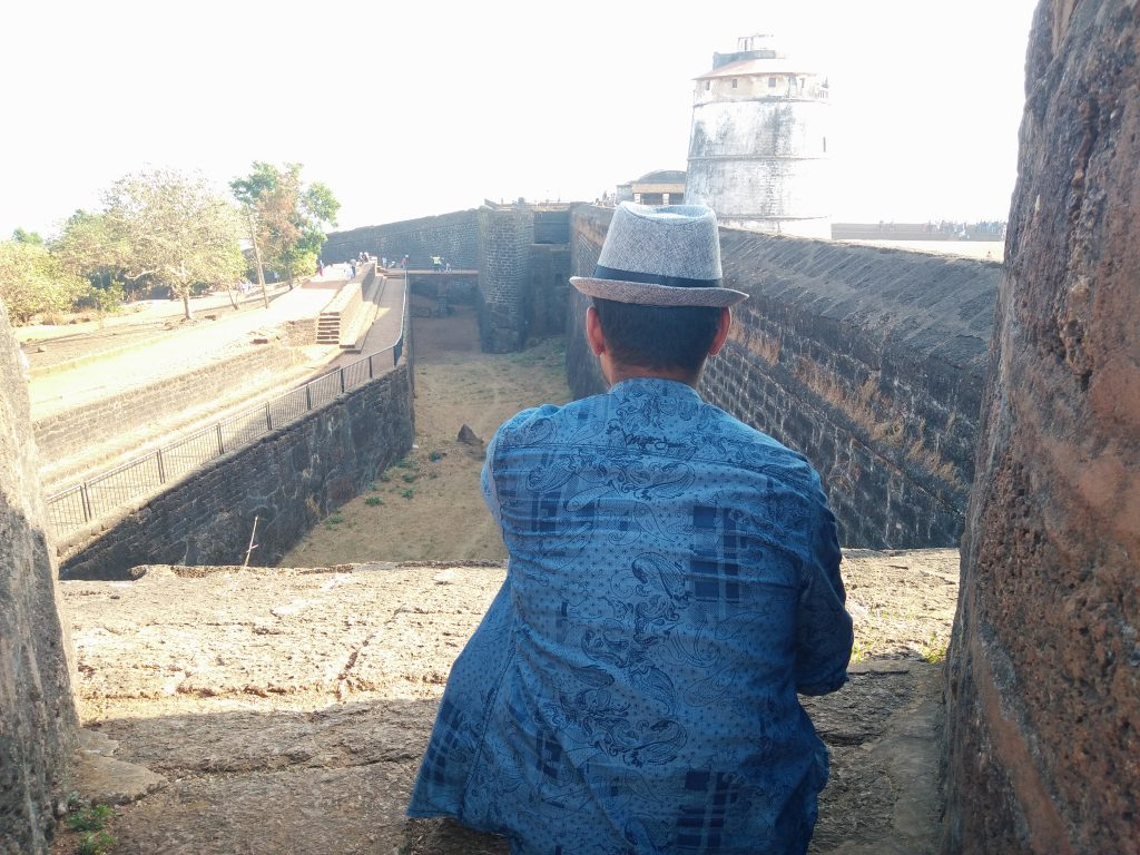 portrait of a man facing the Aguada Fort in Goa